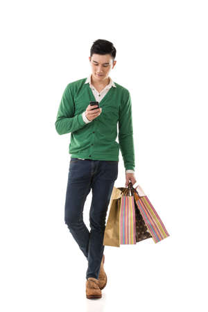 asian guy: Asian young man holding shopping bags and using cellphone, full length portrait isolated.