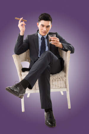 young asian: confident young Asian businessman holding a cigar