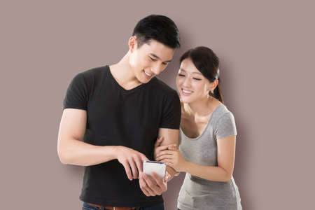asian guy: young Asian couple shopping and looking at cellphone against colorful background Stock Photo
