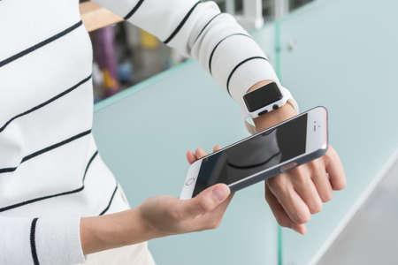 젊은 여자 착용 할 수있는 시계를 사용하여 휴대 전화에 연결 스톡 콘텐츠 - 60015463