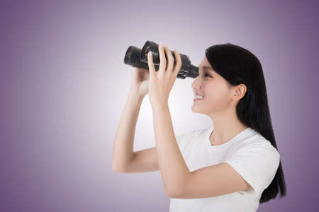 opportunity discovery: woman using binoculars, studio shot portrait