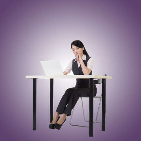computer isolated: Asian business woman sit and work, full length portrait.