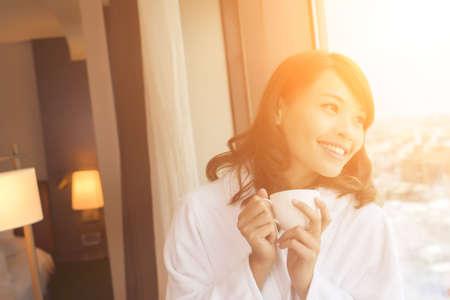 Aziatische vrouw met een kopje koffie in de ochtend.