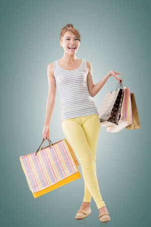 Cheerful shopping woman of Asian holding bags, isolated. Stock Photo