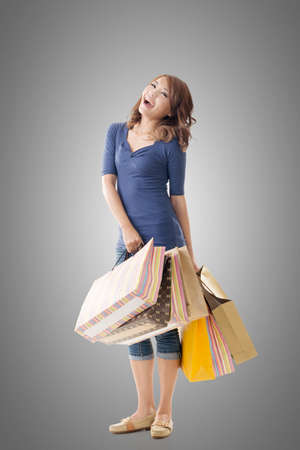 excitation: Cheerful shopping woman of Asian holding bags, full length portrait isolated. Stock Photo