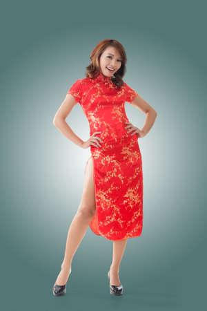 Smiling Chinese woman dress traditional cheongsam at New Year, studio shot isolated. Stock Photo