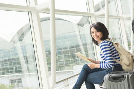 空港待機航空機のアジアの若い女性