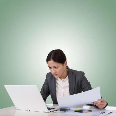 business concern: Worried business woman of Asian using laptop on desk, closeup portrait.