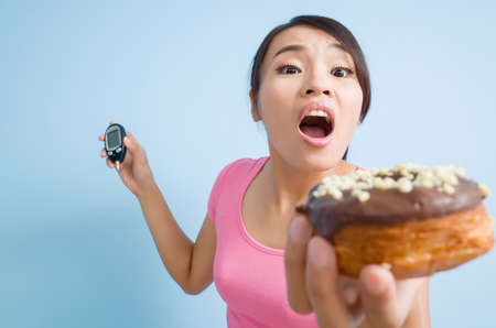 blood glucose meter: asian woman hold a blood glucose meter and a donut