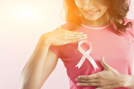 healthcare and medicine concept - woman with pink breast cancer awareness ribbon