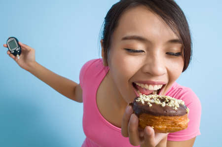 glucose: asian woman hold a blood glucose meter and a donut