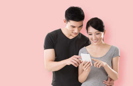asian lifestyle: young Asian couple shopping and looking at cellphone against colorful background Stock Photo