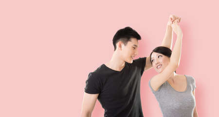 parejas de jovenes: young Asian couple dancing with smiling face against colorful background Foto de archivo
