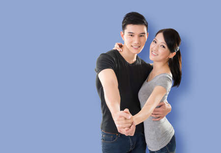 young Asian couple dancing with smiling face against colorful background Stock Photo