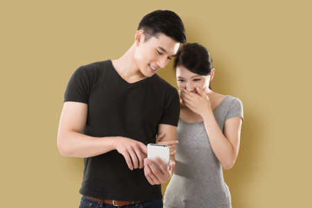 young Asian couple shopping and looking at cellphone against colorful background photo