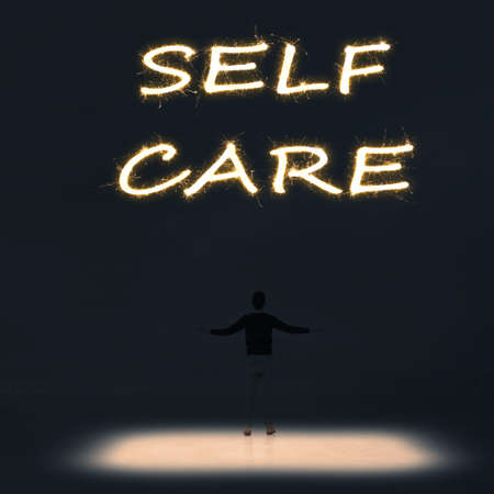 autocuidado: Concept of self care with a person stand in the outdoor and looking up the text over the sky in the night.