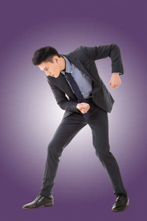 Digging pose or using shovel, full length portrait of Asian young business man. Stock Photo