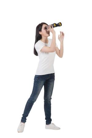see through: woman using binoculars, studio shot portrait