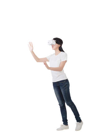 Woman using the virtual reality headset, full length portrait isolated on white Stock Photo