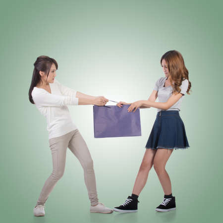 girl fighting: Two Asian girl fighting for shopping bags.