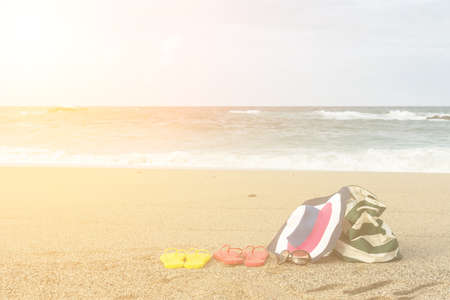 shore: Summer concept of bag and flip flops on a tropical beach. Stock Photo