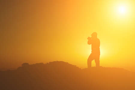 outside: A silhouette of cameraman with golden light in the morning. Stock Photo