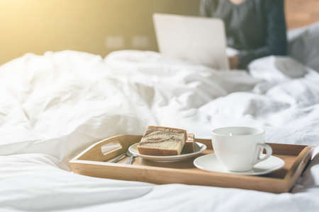 concepto de trabajo en casa con la mujer usando la computadora portátil en la cama