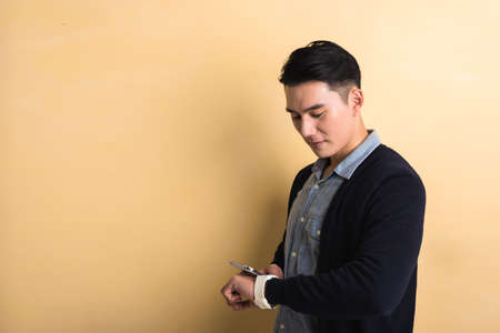 japanese people: handsome Asian young man using smart watch and phone, shot at studio yellow background