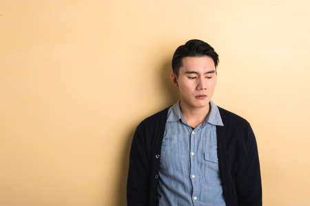 trouble: sad Asian young man in the studio yellow background