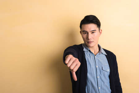 disapprove: young man give you a gesture of bad, shot at studio yellow background Stock Photo