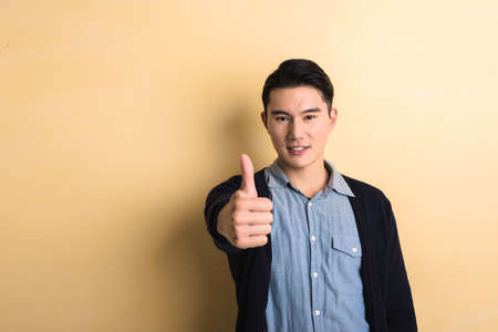 admire: young man give you a gesture of good, shot at studio yellow background Stock Photo