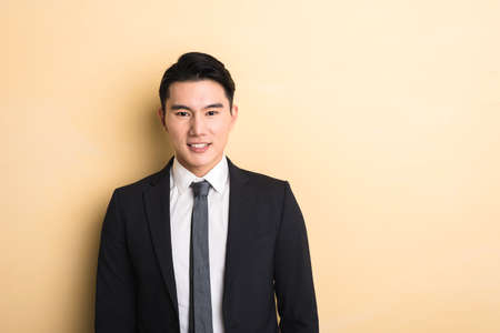 korean man: young Asian business man, closeup portrait on studio yellow background