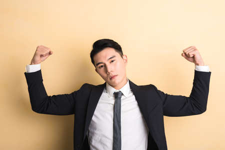 portrait man: young Asian business man show you his muscle, closeup portrait on studio yellow background