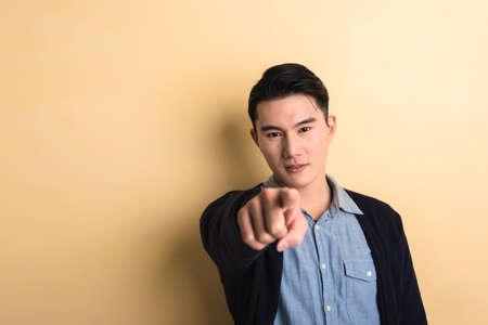 communicating: young man give you a gesture of point at you, shot at studio yellow background Stock Photo