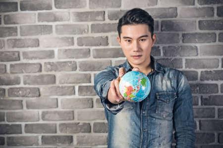 uomo felice: Asian young man hold a globe ball