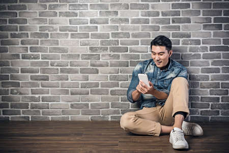 asian guy: young Asian man sit on ground and using smartphone Stock Photo