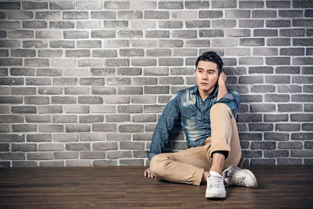 lonely person: young Asian man sit on ground feel lonely