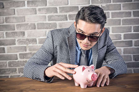 greediness: greedy businessman look at the pink pig bank