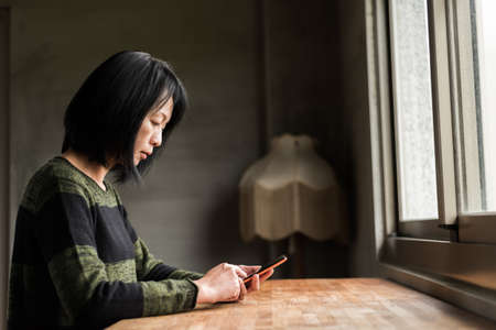 Asian woman using cellphone in the house