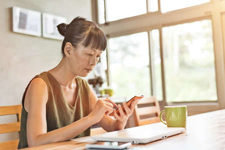 Asian mature woman using smartphone at home