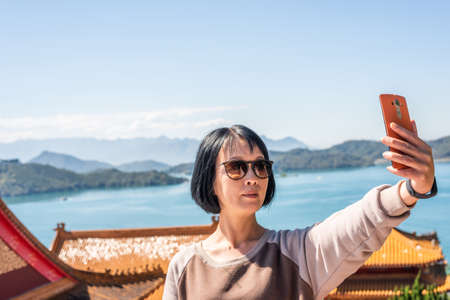 Asian woman take a selfie at Wenwu temple, Nantou, Taiwan