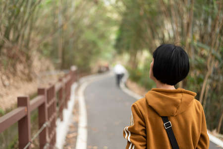 rear view of Asian woman walk on a path at outdoor