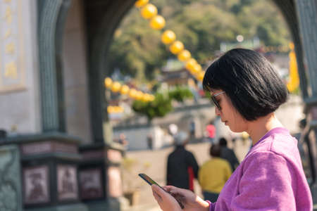 mature Asian woman using the cellphone at a temple