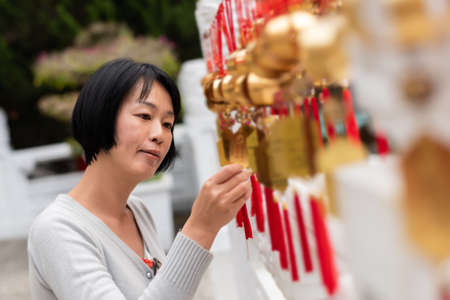 traveling woman look at the golden bells of wish wall on Wenwu Temple, Taiwan