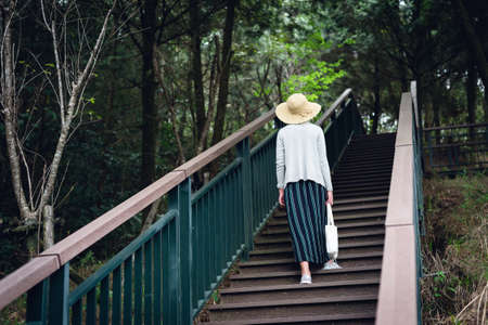 Asian woman walking at the stairs in the outdoor forest