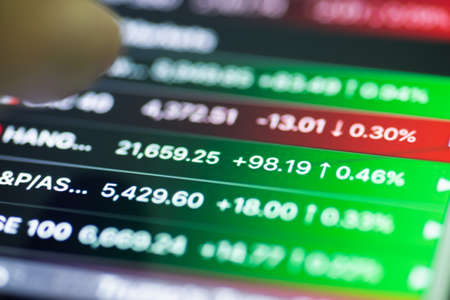 macro view of man using stock market application on touchscreen smartphone, shallow depth of focus
