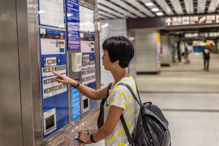 Taipei, Taiwan - May 10th, 2019:woman buying at ticket machine in the train station, Taipei, Taiwan, Asia
