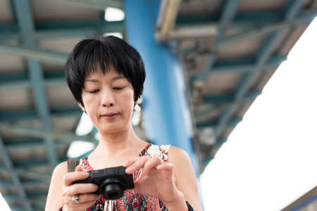 Asian woman using digital camera at a train platform in the outside
