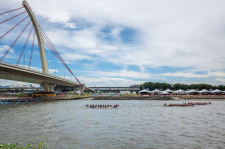 Taipei, Taiwan - Jun 9th, 2019: city scenery with competitive boat racing under the bridge in the traditional Dragon Boat Festival in Taipei, Taiwan, Asia Imagens - 124999009