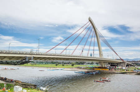 Taipei, Taiwan - Jun 9th, 2019: city scenery with competitive boat racing under the bridge in the traditional Dragon Boat Festival in Taipei, Taiwan, Asia Редакционное